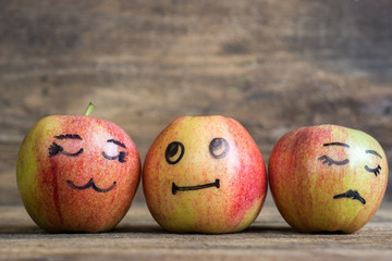 Face on an apples. Apple family on wooden background. Room for text