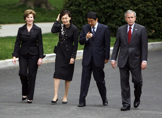 Japan's PM Shinzo Abe wipes his eye as he and his wife Akie walk with U.S. President George W. Bush and First Lady Laura Bush to the North Portico of the White House in Washington