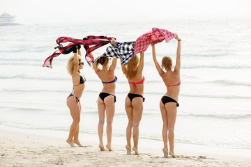 Young sexy girlfriends in bikinis waving their plaid shirts on the beach. Summertime girl fun.