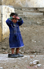 An Afghan girl puts her hands on her face in a Kabul refugee camp.