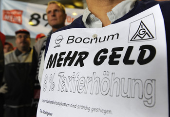 A worker of the Bochum car factory of Opel - Germany's unit of General Motors -carries a placard reading 'more money' as he takes part in an one-hour walkout of members of Germany's metal trade union IG Metall