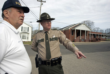 Selmer Police Chief Burks and Tennessee state trooper Killingsworth discuss where to put up media before funeral of murdered minister Winkler outside Fourth Street Church of Christ in Selmer