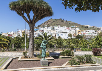 Gardens in public park in Arucas on Gran Canaria, one of the Canary Islands, with town houses on hillside in the background.