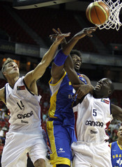 Brazil's Nene fights for a rebound with Canada's Levon Kendall and Denham Brown during the FIBA Americas regional qualifying basketball tournament in Las Vegas