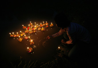 A woman pushes a kratong into a pond during the Loy Kratong festival in Nakhonsawan province