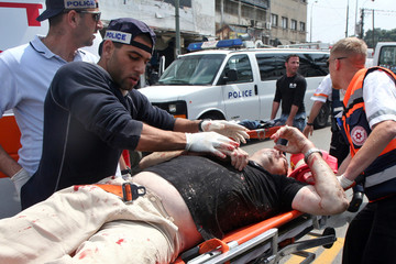 Wounded Israeli civilian is rushed into ambulance, following a suicide attack at Tel Aviv's old central bus station