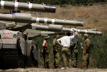 Israeli soldiers take a break beside tanks, near the northern town of Kiryat Shmona on the Israel-Lebanon border