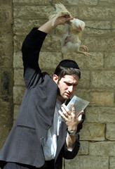 AN ULTRA-ORTHODOX JEW SWINGS A ROOSTER OVER HIS HEAD AS HE PERFORMS THE RITUAL OF KAPAROT, PRIOR TO ...
