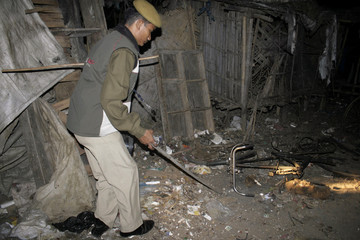 Policeman examines one of bomb blasts sites in Guwahati