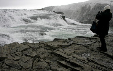 Tourist takes pictures of Gullfoss waterfall in southern Iceland