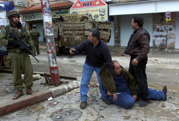 AN ISRAELI SOLDIER STANDS GUARD OVER ARRESTED PALESTINIANS IN RAMALLAH.
