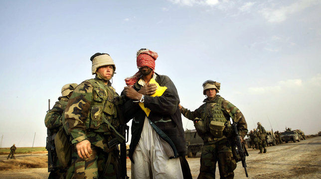 U.S. marines guard detained Iraqi man near a shooting scene in central Iraq March 29, 2003. Confused..