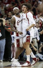 Cleveland Cavaliers' Anderson Varejao of Brazil and LeBron James react to a score in the fourth quarter of play against the Detroit Pistons in Game 4 of the NBA's Eastern Conference basketball series in Cleveland