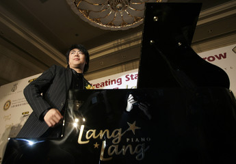 Chinese pianist Lang Lang poses with one of the pianos from the 'Lang Lang Piano Series' during a news conference in Hong Kong