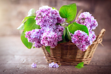 Fotoväggar - Lilac flowers bunch in a basket over blurred wood background