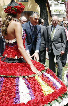 Spanish King Carlos and Portugal's President Silva watch woman wearing adress made out of flowers during visit on Atlantic island of Madeira