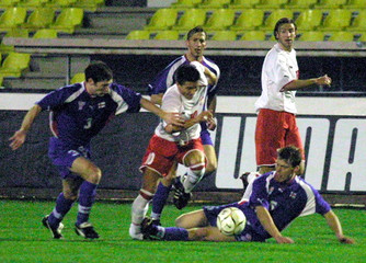 MOSKALA TRIES TO PASS FAORE ISLANDS PLAYERS.