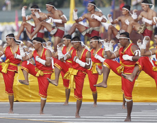 Men dressed in traditional outfits take part in a parade in Bangkok's Royal Plaza