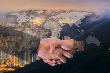 Double Exposure of a businessman handshake on World Global Cartography Globalization with Cityscape Hong Kong Panoramic Night Concept
