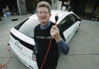 Kramer, founder of CalCars, holds up the electrical cord he uses to charge up his Toyota hybrid car at his home in Redwood city