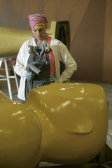 Scenic artist Gayle Etcheverry dries paint on a large Oscar statue near Los Angeles