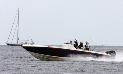 US President Bush and Former President Bush wave from their fishing boat in Kennebunkport