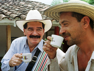 Colombia's coffee icon Juan Valdez (L) shares a cup of coffee with a friend, September 10, 2000. Jua..