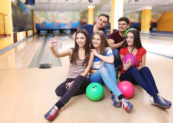 Friends taking selfie in bowling club