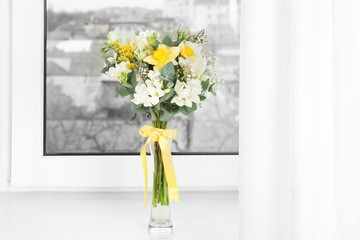 Beautiful bouquet with freesia flowers in vase on window sill