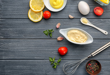 Mayonnaise in gravy boat with ingredients on wooden background, top view