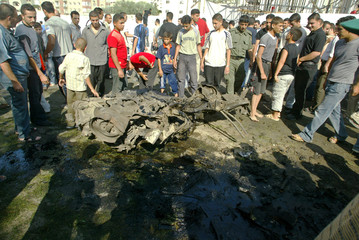 Palestinians gather near the remains of a car after Israeli air strikes in Gaza City.