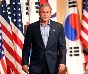 US President Bush enters the room to talk with reporters in Kyongju