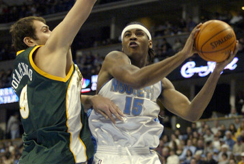 NUGGETS ROOKIE ANTHONY DRIVES AGAINST SUPERSONICS POTAPENKO.
