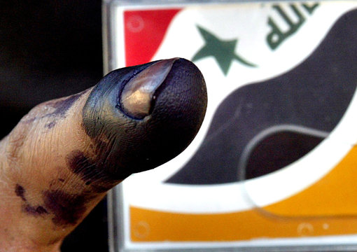 An Iraqi man shows his right index finger stained with blue ink.
