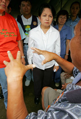 Philippine President Arroyo listens to a landslide survivor at rescue camp near Guinsaugon village in central Philippines