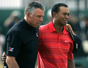 Tiger Woods (R) of the U.S. cries after winning the British Open Championship with his caddy Steve W..