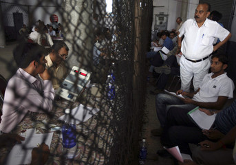 Voting agents keep watch as polling officials count ballots inside counting centre in Jammu