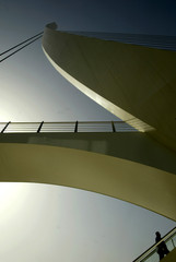 A man walks up the stairs to a pedestrian bridge crossing designed by Spanish architect Calatrava in ...