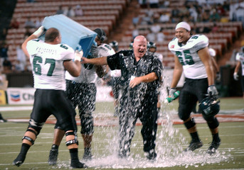 Hawaii offensive's line coach Cavanaugh gets ice bath from players after game in Honolulu.
