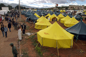 PEOPLE WALK AROUND TENT VILLAGE AFTER EARTHQUAKE IN MOROCCO.