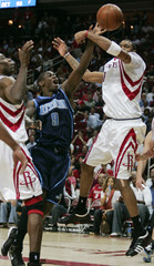 Rockets forward McGrady bats the ball from Jazz guard Brewer as Rockets center Mutombo looks on in the second half as the Rockets beat the Utah Jazz in Game 5 of their NBA basketball playoff series in Houston