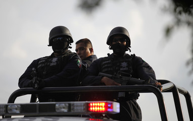 Federal Police stand on a vehicle after arriving in Morelia in Michoacan