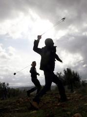 Palestinian youths use slings to hurl rocks at Israeli troops in Bilin
