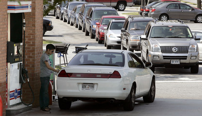 Patrons wait in line to fill their gas tanks at a Kroger fuel station in Lilburn