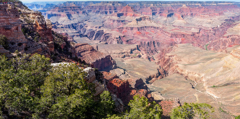 Panoramic view of Grand Canyon at Mather Point, with small people silhouettes on the top of the cliff, showing the vastness of Grand Canyon National Park in Arizona, USA.
