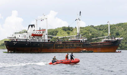 Soldiers on board a rubber dinghy pass the MV Captain UFUK vessel as Customs and Coast Guard officials inspect seized high-powered firearms at the port of Mariveles
