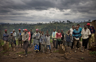 People who live on disputed land at the Mau forest stand by the roadside at a makeshift village