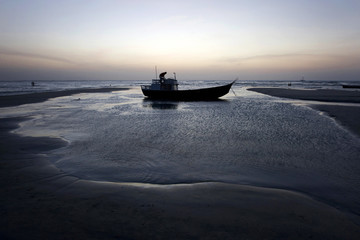 A fisherman works on his boat during low tide after sunset on the beach of Jericoacoara, Brazil