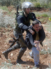 AN ISRAELI BORDER POLICEMAN TRIES TO ARREST A PALESTINIAN PROTESTER IN WEST BANK.
