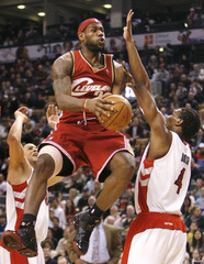 Cleveland Cavaliers forward LeBron James goes to the basket against Toronto Raptors Parker and Bosh in Toronto